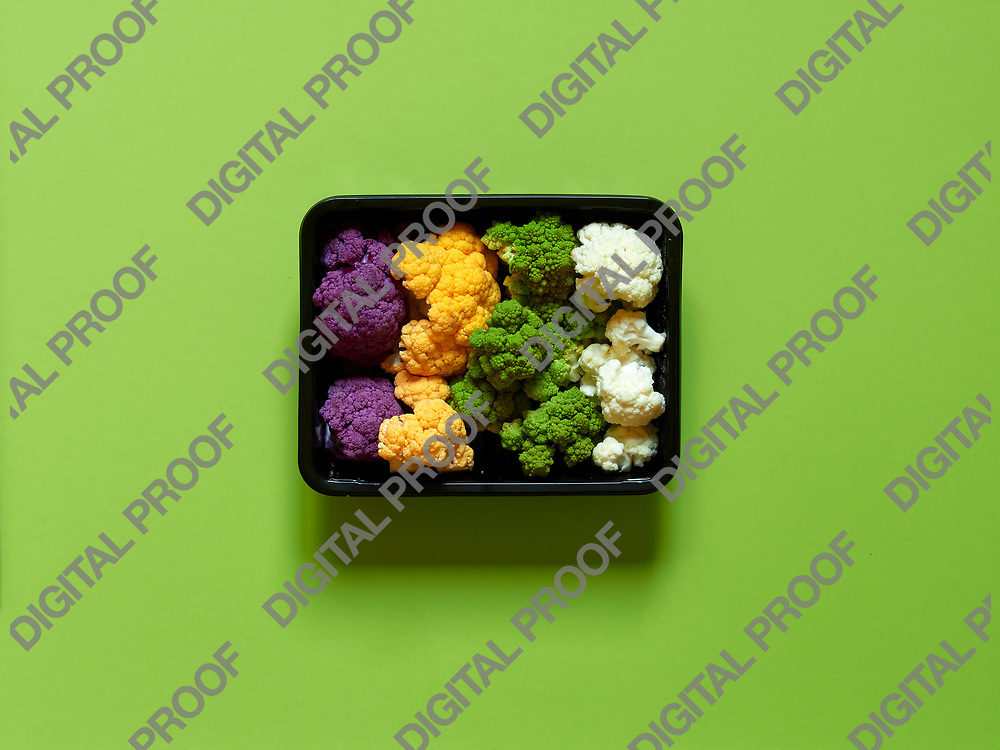 Set of seasonal and colorful cauliflower violet, yellow, green and white boxed in a plastic recipient over a lime green background