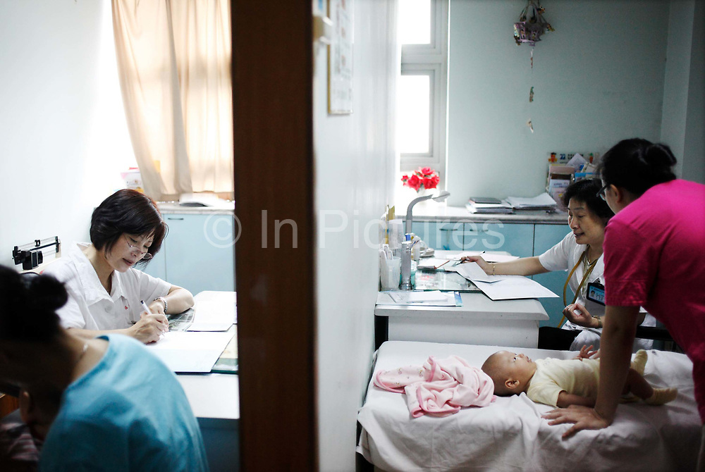 Parents take their kids to a health checkup at a clinic in Shanghai, China on 26 June 2009. Despite China's plan to increase spending in healthcare as a way of fiscal stimulus, future of China's healthcare remains bleak as hundreds of millions of rural residence lack proper insurance and hospitals rely on prescribing expensive and often unnecessary drugs as means of income. Drugs account for over 60% of medical spending in China, compared to 12% world average, and bring in over half of hospital income.