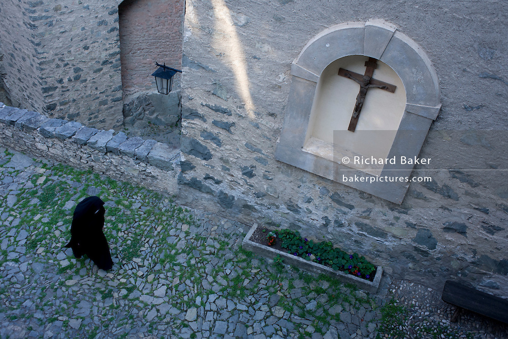 A nun walks through the courtyard at Säben Abbey in Klausen, South Tyrol, Italy. Säben Abbey is a Benedictine nunnery established in 1687, when it was first settled by the nuns of Nonnberg Abbey in Salzburg.