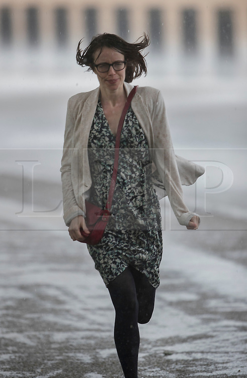 © Licensed to London News Pictures. 12/07/2016. London, UK. A woman runs as a sudden rain storm hits central London. Photo credit: Peter Macdiarmid/LNP