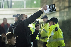 """© Licensed to London News Pictures . 03/11/2017 . Manchester , UK . A man with a copy of Robinson's book gestures towards a counter protest organised by Unite Against Fascism . Fans of Tommy Robinson (real name Stephen Yaxley-Lennon ) and anti-fascist counter demonstrators at the launch of the former EDL leader's book """" Mohammed's Koran """" at Castlefield Bowl . Originally planned as a ticket-only event at Bowlers Exhibition Centre , the launch was moved at short notice to a public location in the city . Photo credit : Joel Goodman/LNP"""