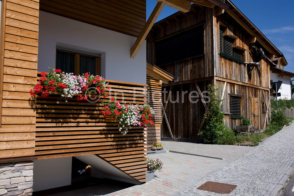 Modern Tyrolean house architecture in Leonhard-St Leonardo, a Dolomites village in the Badia region of south Tyrol, Italy. Wooden panelling and slats have been retained as the traditional style of the area has seen over centuries. Life expectancy for south Tyroleans is 85 for females and 80 for males, higher than Italian national averages. According to the 2011 census, there are 505,000 inhabitants in south Tyrol, the same as Dublin, Copenhagen and Dresden. In the 2011 census, 91.3% of the population speak German, 7.9% Italian and 0.8% spoke the ancient Ladin langauge as their mother tongue. San Leonardo is in the municipality of Badia populated mostly by people who speak the ancient Ladin language.