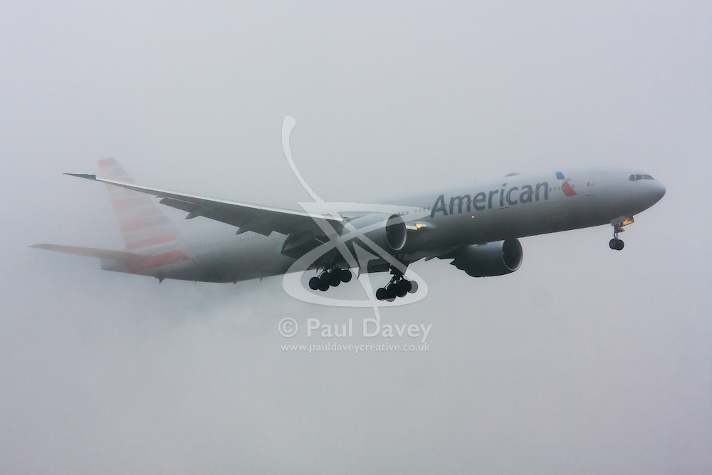 """January 3rd 2015, Heathrow Airport, London. Low cloud and rain provide ideal conditions to observe wake vortexes and """"fluffing"""" as moisture condenses over the wings of landing aircraft. With the runway visible only at the last minute, several planes had to perform a """"go-round"""", abandoning their first attempts to land. PICTURED: Water streaming from its wings, an A merican Airlines Boeing 777 prepares to land on Heathrow's runway 27L."""