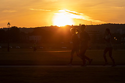 © Licensed to London News Pictures. 23/09/2021. London, UK. Members of the public exercise during sunrise on Blackheath Common in South East London. Temperatures are expected to rise with highs of 22 degrees forecasted for parts of London and South East England today . Photo credit: George Cracknell Wright/LNP