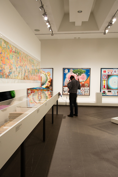 """A gallery in The American Folk Art Museum, with Paul Laffoley's """"The Principles of Alchemy. Part I: the corporeal"""" on the back wall."""