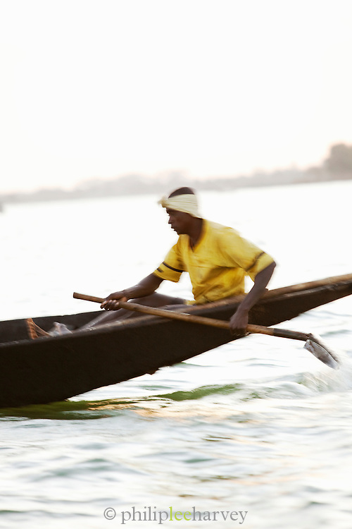 A sand diver steers his boat early in the morning on the Niger River at Segou, Mali. People dive to the bottom of the river, filling buckets with sand to be used in construction all over the country. Many people die each year doing this dangerous job