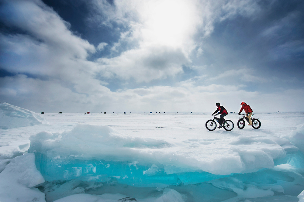 Fat tire riding on frozen Lake Superior in Spring as ice begins to pile while ice fishing take their changes in ice houses along the ice.