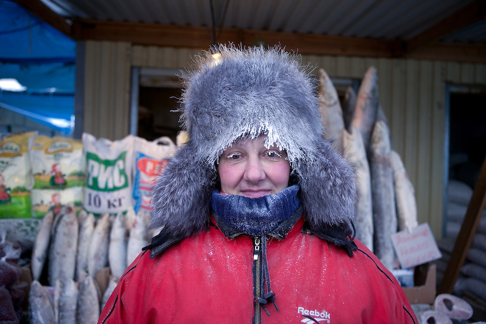Portrait of a women selling frozen fish on the Yakutsk outdoor fish market. Yakutsk is a city in the Russian Far East, located about 4 degrees (450 kilometres) south of the Arctic Circle. It is the capital of the Sakha (Yakutia) Republic in Russia with a major port on the Lena River. The city has a population of 264.000 (2009). Yakutsk is one of the coldest cities on Earth. The average monthly winter temperature in January is around -43,2 C. Yakutsk, Jakutsk, Yakutia, Russian Federation, Russia, RUS, 16.01.2010.