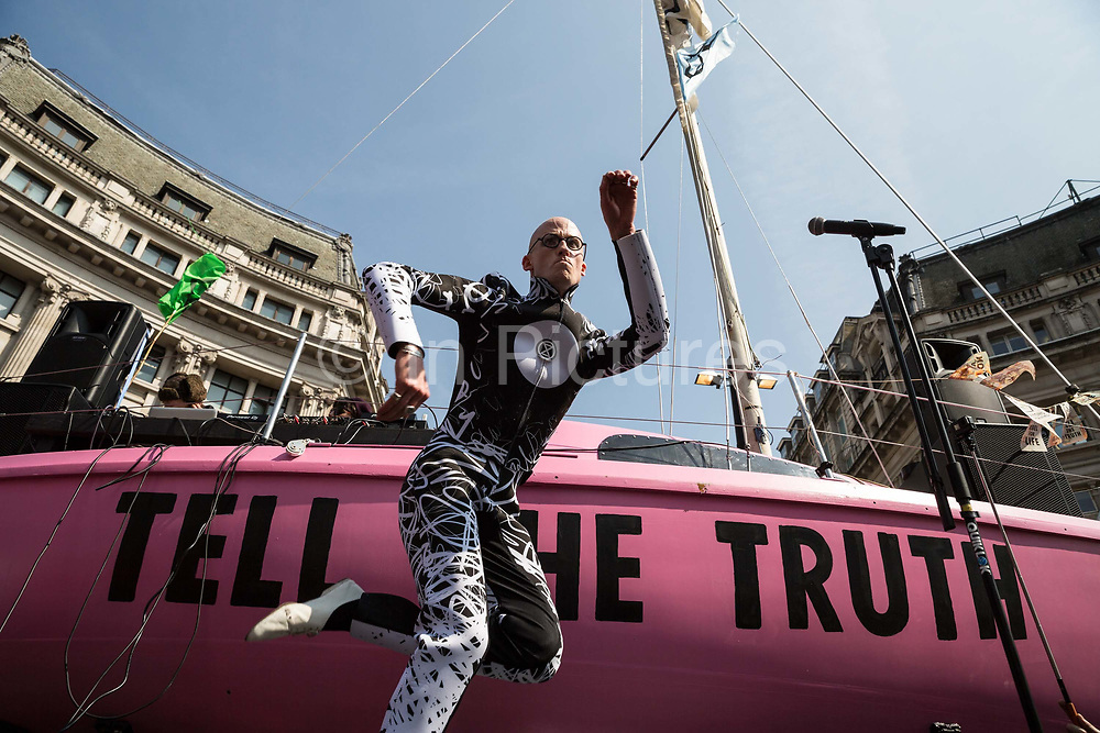 Mr Bruce, from Electro duo The Correspondents, dances on stage in front of a pink yacht during a protest against climate change in the middle of Oxford Circus on 15th April, 2019 in London, United Kingdom.  Extinction Rebellion have blocked five central London landmarks in protest against government inaction on climate change. .