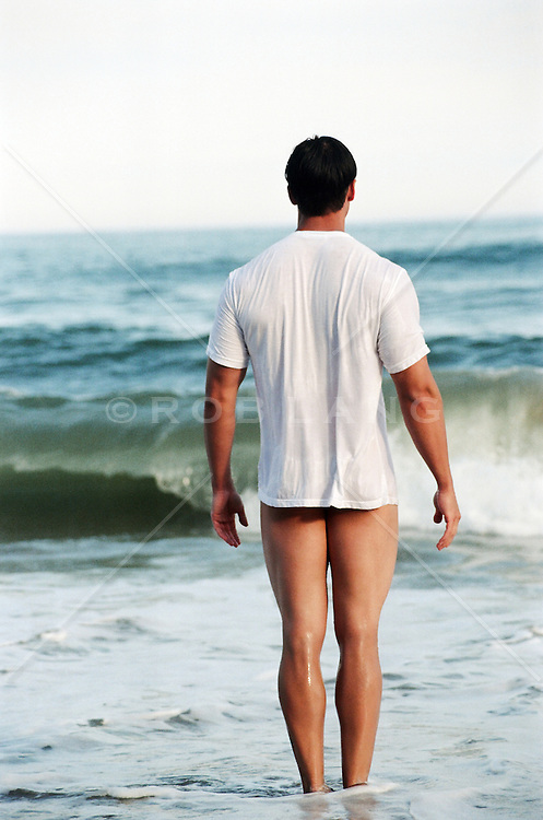 man wearing only a tee shirt at the ocean in Montauk, NY
