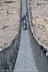Bear Haughton riding across a narrow suspension bridge over the Kali Gandaki River on day-6 of our Himalayan Heroes adventure riding from Muktinath to Tatopani, Nepal. Sunday, November 11, 2018. Photography ©2018 Michael Lichter.