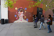Teenagers walk past the mural of iconic musician and singer David Bowie has appeared on the wall of Morleys department store in Brixton, Lambeth, south London. The Bowie face is sourced (by artist James Cochran, aka Jimmy C) from the cover of his 1973 album Aladdin Sane at the height of his 1970s fame. The pop icon lived at 40 Stansfield Road, Brixton, from his birth in 1947 until 1953. This cover appeared in Rolling Stone's list of the 500 greatest albums of all time, making #277.