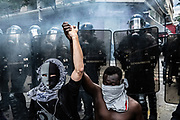 Parijs, Frankrijk, 13/06/20 | Two protesters hold hands in the mids of clashes between French riot police and protesters during a Black Lives Matter protest in Paris.