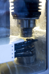 SOLMS, GERMANY - MAY-18-2009 - A puck of raw glass, which will eventually be an element of the Leica 21mm F-1.4 lens, is ground in a computer controlled grinding machine. The specialized machine can shave fractions of millimeters to attain the perfect optical specifications required for Leica lenses. Leica buys it's glass from most of the major glass manufactures around the world, depending on optical purity, availability and price. (Photo © Jock Fistick)