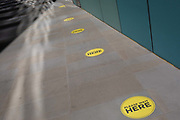 Yellow circular social distance markers are spaced out along a pedestrian path in the City of London, the capitals financial district, on 31st July 2020, in London, England.