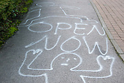 France. Calais Port. White paint grafitti on pavement with words 'Open Now'.