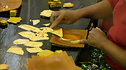 Woman at the King Galon factory in Mandalay creating gold leaf squares to be applied to the various Buddha statues in Myanmar