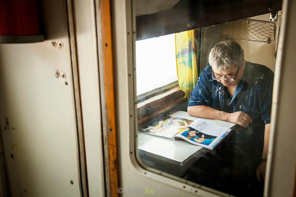 Inside a cabin a man reads on-board the BAM (Baikal-Amur Mainline) Siberia, Russia