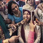 """Women relatives of the Sikh groom feed him with some """"laddoo"""" sweets before his baraat. As per Sikh tradition, the groom must wear a turban, sehra (which is a beed or flower veil over his face) and carry a sword (kripan). He must also sport a beard, even if he is a clean-shaven Sikh. Chandigarh 2011"""