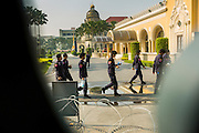 """09 DECEMBER 2013 - BANGKOK, THAILAND: Thai riot police walk past Government House in Bangkok. Thai Prime Minister Yingluck Shinawatra announced she would dissolve the lower house of the Parliament and call new elections in the face of ongoing anti-government protests in Bangkok. Hundreds of thousands of people flocked to Government House, the office of the Prime Minister, Monday to celebrate the collapse of the government after Yingluck made her announcement. Former Deputy Prime Minister Suthep Thaugsuban, the organizer of the protests, said the protests would continue until the """"Thaksin influence is uprooted from Thailand."""" There were no reports of violence in the protests Monday.      PHOTO BY JACK KURTZ"""