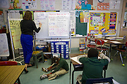 Third-grader Tyra McGhee sits on the floor to do work as volunteer Hannah O'Brien explains a writing exercise at Adelaide Davis Elementary School on Nov. 26, 2012 in Washington, D.C. Last week DCPS Chancellor Kaya Henderson proposed closing 20 under-enrolled schools in the District. Davis Elementary is one of 20 schools in the DCPS system included in the school closure proposal. There are currently 178 students enrolled in Davis Elementary and the second floor of the school is only used for music classes and the library...CREDIT: Lexey Swall for The Wall Street Journal.DCSCHOOLS