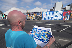Mural Artist Lyonsi looks at a plan for a huge NHS Mural on Belfast's Falls Road, a collaboration between artistss Lyonsi and Micky Doc.