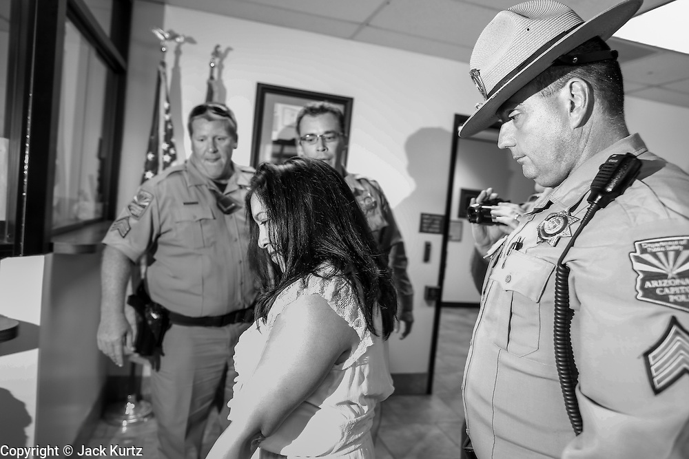 17 OCTOBER 2013 - PHOENIX, AZ:     A person is arrested by Arizona Capitol Police in the office of the Attorney General. About 100 people came to the office of Arizona Attorney General Tom Horne to protest the decision by Horne to sue community colleges in Maricopa County that charge DREAM Act students who are residents of Arizona out of state tuition rather than in state resident tuition. Nearly 10 people were arrested in a planned civil disobedience during the protest.   PHOTO BY JACK KURTZ