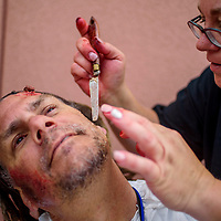 Scott Halliday, left, has trauma makeup applied by Lanee Forkner before playing a mock victim in an emergency exercise at RMCH in Gallup Saturday.