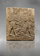 Hittite sculpted Orthostats panel of Long Wall Limestone, Karkamıs, (Kargamıs), Carchemish (Karkemish), 900-700 B.C. Soldiers. Anatolian Civilisations Museum, Ankara, Turkey<br /> <br /> Figure of two helmeted warriors. They have their shield in their back and their spear in their hand. The prisoner in their front is depicted small. A human head is depicted in the left hand of the warrior in the front. The warrior at the rear holds the prisoners sitting on his lap from his hair. Below this figure, which was described small, lies yet another small human figure. <br /> <br /> On a grey art background. .<br />  <br /> If you prefer to buy from our ALAMY STOCK LIBRARY page at https://www.alamy.com/portfolio/paul-williams-funkystock/hittite-art-antiquities.html  - Type  Karkamıs in LOWER SEARCH WITHIN GALLERY box. Refine search by adding background colour, place, museum etc.<br /> <br /> Visit our HITTITE PHOTO COLLECTIONS for more photos to download or buy as wall art prints https://funkystock.photoshelter.com/gallery-collection/The-Hittites-Art-Artefacts-Antiquities-Historic-Sites-Pictures-Images-of/C0000NUBSMhSc3Oo