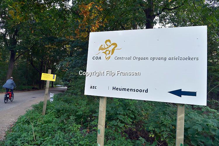 Nederland, Nijmegen, 1-10-2015 Toegang tot AZC heumensoord. Met hoge snelheid worden de tenten gebouwd voor de noodopvang van 3000 asielzoekers in natuurgebied Heumensoord. De vluchtelingen, worden hier tijdelijk gehuisvest in een tentenkamp tot uiterlijk 1 juni 2016. In 1998, werd er ook een noodkamp gevestigd. Destijds werd op Heumensoord onderdak geregeld voor een kleine 1.000 asielzoekers. Nijmegen, the Netherlands, 1-10-2015 In Holland the growing number of refugees forces the government to house them temporary and improvised in unused or empty buildings and halls. Often these are rented from private owners or real-estate firms. In this case a tent camp is erected in a wooded area near the city of Nijmegen. The tents are also used during the famous four days marches on this location. FOTO: FLIP FRANSSEN/ HH