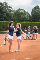 Young women stretching on tennis court on a sunny day, Bavaria, Germany