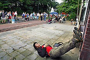 Nederland, Nijmegen, 17-7-2008Vierdaagse, de dag van Groesbeek. Traditioneel de zwaarste vanwege de zevenheuvelenweg die een vijftal heuvels heeft tussen Groesbeek en Berg en Dal. Hier de doorkomst in Berg en Dal. Een loper uit Zwitserland laat zijn benen rusten tegen de gevel van een huis. Foto: Flip Franssen/Hollandse Hoogte