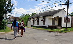 29 May 2014. New Orleans, Louisiana.<br /> The forlorn street corner at Eads and N Rocheblave Streets. A 17 year old male was shot and killed May 26th near this corner. There is no memorial marker for where the slain teenager fell. Less than a block away there is roadside memorial for a dog at the corner of N. Rocheblave and Franklin Ave. The dog killed was knocked down and killed in the street 2 weeks earlier. Memorial for a dog - not for a teenager........go figure.<br /> Charlie Varley/varleypix.com