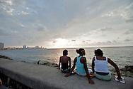Cuban children relaxing on the Malecon seawall at sunset in Havana, Cuba.
