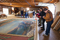 Gerry Horn, Robert Fortier and Yvonne Horn look on from the far end of the drape while Christine Hadsel and Warren Huse makes notes on the hand painted curtain found in the Lakeport Opera House.  (Karen Bobotas/for the Laconia Daily Sun)