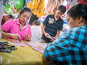 """27 NOVEMBER 2012 - BANGKOK, THAILAND:  Women play bingo in the Bingo tent at the Wat Saket Temple Fair in Bangkok. Bingo is called Bingo in Thailand. Wat Saket, popularly known as the Golden Mount or """"Phu Khao Thong,"""" is one of the most popular and oldest Buddhist temples in Bangkok. It dates to the Ayutthaya period (roughly 1350-1767 AD) and was renovated extensively when the Siamese fled Ayutthaya and established their new capitol in Bangkok. The temple holds an annual fair in November, the week of the full moon. It's one of the most popular temple fairs in Bangkok. The fair draws people from across Bangkok and spills out in the streets around the temple.   PHOTO BY JACK KURTZ"""