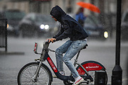 A person cycles through a torrential rain that downpoured Britain's capital near Westminster Palace, Houses of Parliament on Sunday, Aug 8, 2021. Some say that London weather can be one of two things: abjectly miserable or incomparably wonderful. There is no in-between. (VX Photo/ Vudi Xhymshiti)