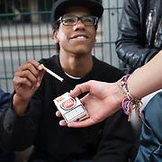 Nederland Rotterdam 13-10-2010 20101013.Jongeren chillen op bankje en roken een sigaret, rokende jongeren. Jongen biedt sigaret aan vriend aan. Young people smoking cigarettes and chilling. Holland, The Netherlands, dutch, Pays Bas, Europe ..Foto: David Rozing