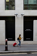 A Londoner walks beneath two CCTV cameras in the City of London, one of the most-watched  on 11th August, 2017, in London, England. According to 2011 figures, there are 420,000 CCTV cameras in London.