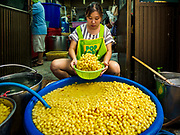 """07 FEBRUARY 2018 - BANGKOK, THAILAND: A woman in Bangkok's """"Chinatown""""  sorts boiled mung beans for desserts consumed during Lunar New Year celebrations. The Lunar New Year, also called Tet or Chinese New Year, is 16 February this year. The coming year will be the Year of the Dog. Thailand has a large Chinese community and Lunar New Year is widely celebrated in Thailand, especially in Bangkok and large cities with significant Chinese communities.      PHOTO BY JACK KURTZ"""