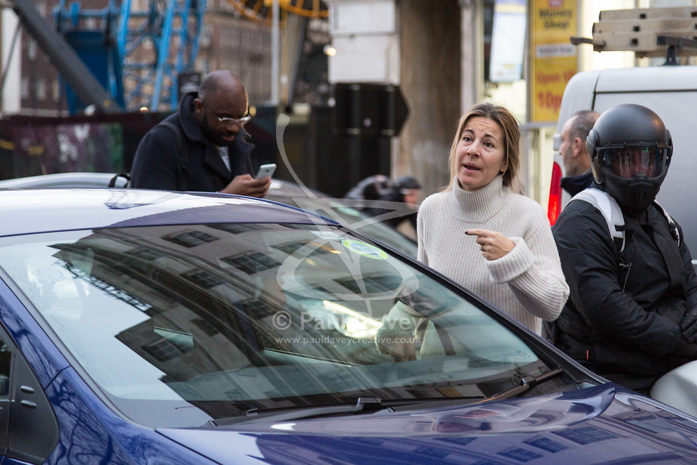 PICTURED: A woman remonstrates with protesters as she is held up in traffic. Demonstrators from the anti-pollution group Stop Killing Londoners cause traffic chaos for London commuters as they conduct a series of short roadblocks at Marble Arch stopping cars and buses from entering Oxford Street and Park Lane. Irate motorists accused them of creating more pollution than they were stopping, whilst the group said their objectives were long term. A leaflet handed out to motorists says the government is not doing enough to tackle the crisis costing 'taxpayers and the NHS £billions [sic] a year'. PLACE, January 29 2018. © Paul Davey