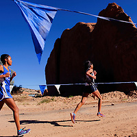 100414       Cable Hoover<br /> <br /> Navajo Pine Warrior Annoesika Laughlin tries to chase down race leader Chamique Duboise near the midpoint of the Gallup Invitational cross country meet at Red Rock Park Saturday.