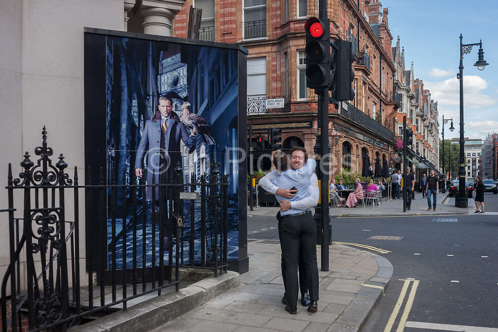 Two friends in a man hug in front of a construction hoarding featuring a male with a bird of prey on his arm, on 23rd September 2016, in Mayfair, central London, England.