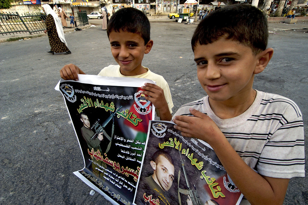 Two Palestinian boys in Nablus hold posters of Tayseer Yousef Sihab, a Palestinian militant who died fighting Israeli troops occupying Nablus in May 2002.