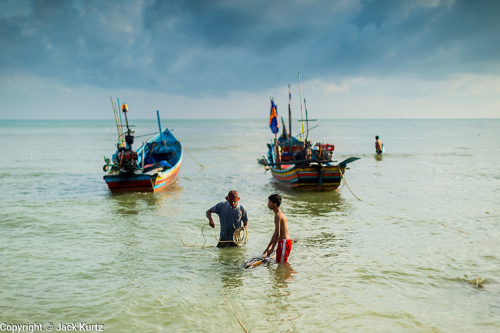 07 FEBRUARY 2014 - KAO SENG, SONGKHLA, THAILAND:  Fishermen come to shore after landing their boats in Kao Seng. Kao Seng is a traditional Muslim fishing village on the Gulf of Siam near the town of Songkhla, in the province of Songkhla. In general, their boats go about 4AM and come back in about 9AM. Sometimes the small boats are kept in port because of heavy seas or bad storms.     PHOTO BY JACK KURTZ