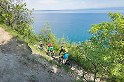 Mountain bikers riding through dirt road on cliff by sea