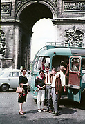 Three young people two men a woman standing by open bus door entrance older woman nearby, Arc de Triomphe, Paris, France c 1960