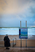 Plage non surveillee. Beach not supervised. A woman watches as Atlantic waves lash the resort town of Biarritz, in the Basque region of France, March 2013