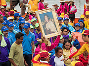 "23 JUNE 2015 - MAHACHAI, SAMUT SAKHON, THAILAND: A man getting off a fishing boat carries a portrait of Princess Maha Chakri Sirindhorn, the Crown Princess of Thailand, at the City Pillar Shrine procession in Mahachai. People get off a fishing boat during the procession for the City Pillar Shrine in Mahachai. The Chaopho Lak Mueang Procession (City Pillar Shrine Procession) is a religious festival that takes place in June in front of city hall in Mahachai. The ""Chaopho Lak Mueang"" is  placed on a fishing boat and taken across the Tha Chin River from Talat Maha Chai to Tha Chalom in the area of Wat Suwannaram and then paraded through the community before returning to the temple in Mahachai.   PHOTO BY JACK KURTZ"