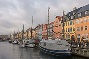 Nyhavn harbour on the 19th November 2017 in Copenhagen, Denmark. Nyhavn is a 17th-century waterfront, canal and entertainment district in Copenhagen. Stretching from Kongens Nytorv to the harbour front just south of the Royal Playhouse, it is lined by brightly coloured 17th and early 18th century townhouses and bars, cafes and restaurants. The canal harbours many historical wooden ships.